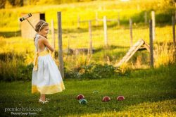 Flower girl playing croquet at a farm wedding