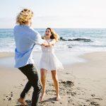 fun couple dances on beach