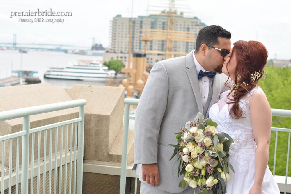 Bride and groom his by Philadelphia shore