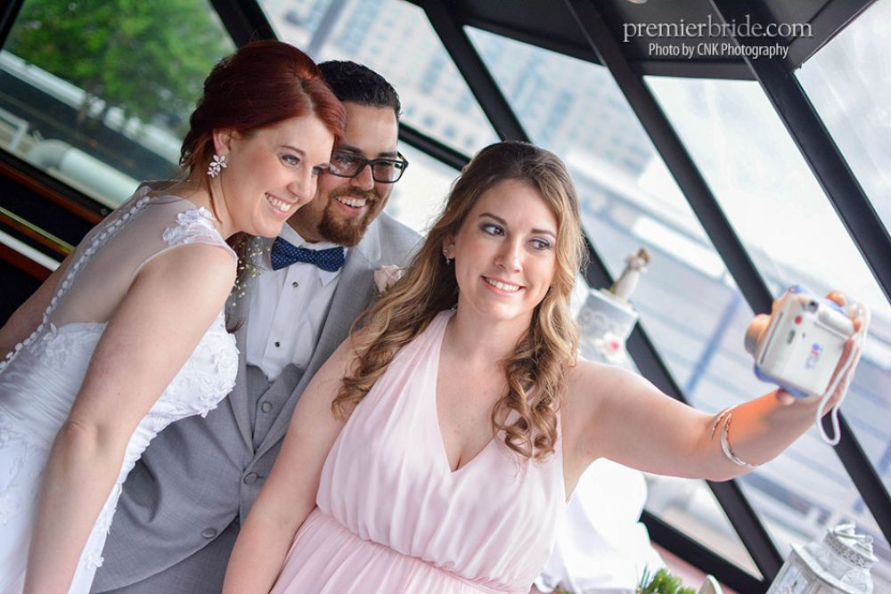 Bridesmaid taking a selfie with the bride and groom