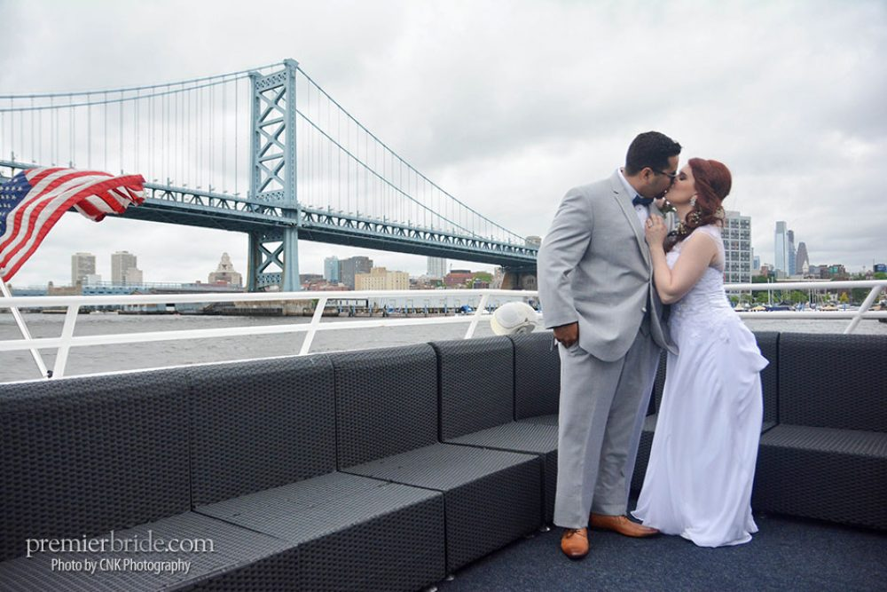 Bride and groom kiss by Ben Franklin bridge